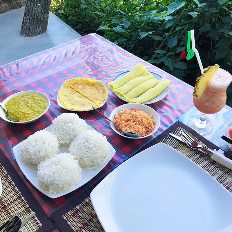 Delicious home made breakfast of string hoppers, coconut pancake rolls, coconut sambal, omelettes and juice! In Ella, Sri Lanka. | www.achronicvoice.com